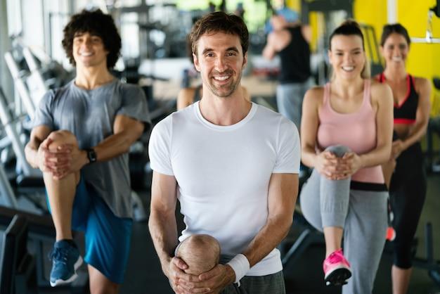 Groupe de personnes en bonne santé au gymnase faisant de l'exercice