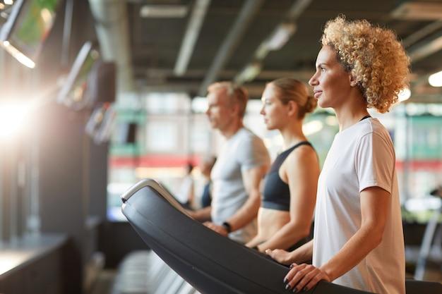 Groupe de personnes en bonne santé exerçant sur des tapis roulants pendant l'entraînement sportif au club de santé