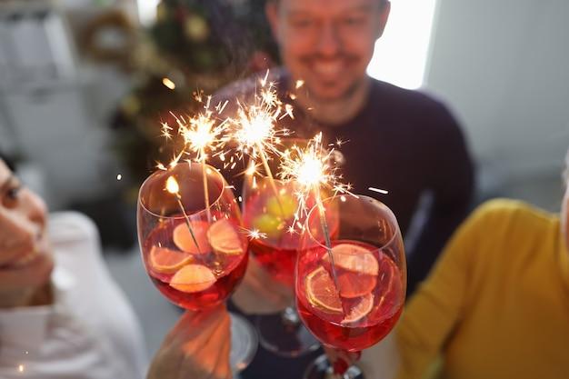 Groupe de personnes buvant des cocktails dans des verres avec des cierges magiques devant un arbre de noël en gros plan
