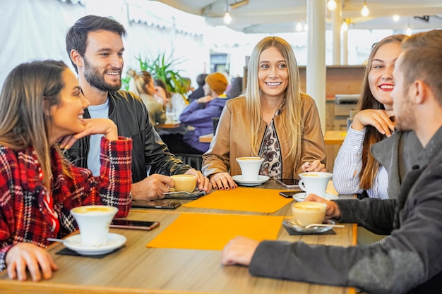 Groupe de personnes buvant du cappuccino dans un bar