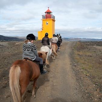 Groupe de personnes chevauchant des chevaux islandais le long d'un sentier menant au phare