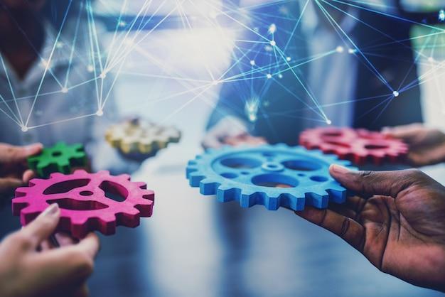 Un groupe de personnes connecte des roues dentées de couleur unique pour fabriquer un engrenage.
