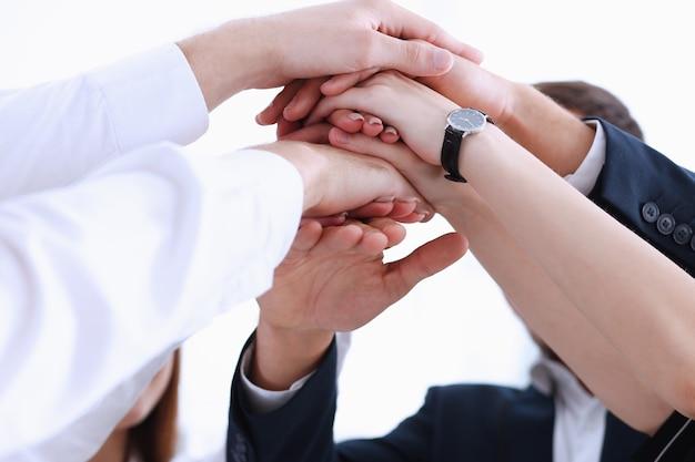 Groupe de personnes en costume croisé les mains en tas