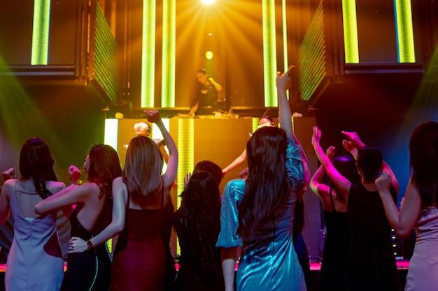 Groupe de personnes dansent dans une discothèque au rythme de la musique du dj sur scène