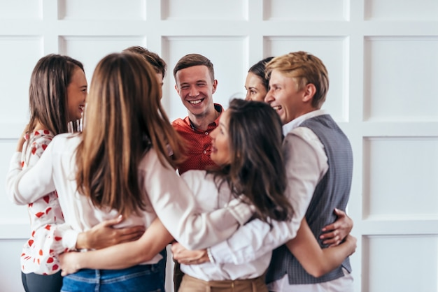 Groupe de personnes debout en cercle dans une formation de croissance personnelle.