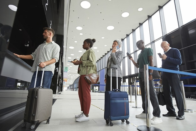 Groupe de personnes debout dans une rangée à la billetterie de l'aéroport