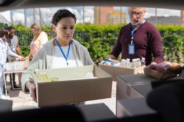 Groupe de personnes différentes faisant du bénévolat dans une banque alimentaire pour les pauvres