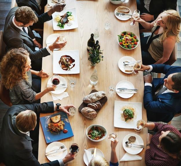 Groupe de personnes diverses déjeunant ensemble