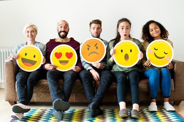 Groupe de personnes diverses détenant des icônes d'émoticônes