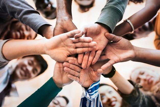 Groupe de personnes diverses empilant les mains au milieu