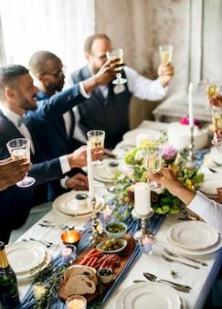 Groupe de personnes diverses tinter les verres à vin ensemble