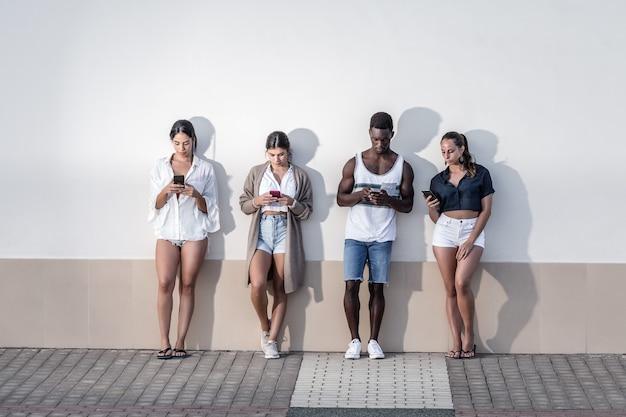 Groupe de personnes diverses utilisant des smartphones dans la rue de la ville