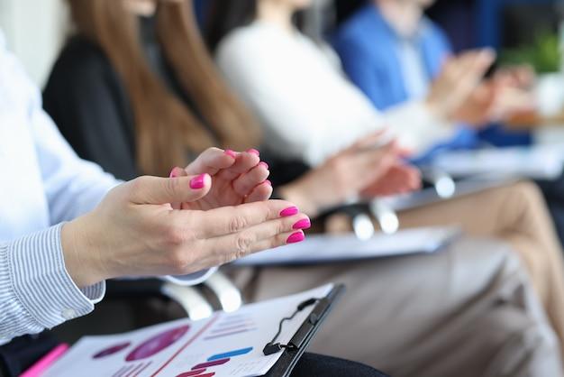 Groupe de personnes avec des documents applaudissant lors d'une conférence d'affaires en gros plan