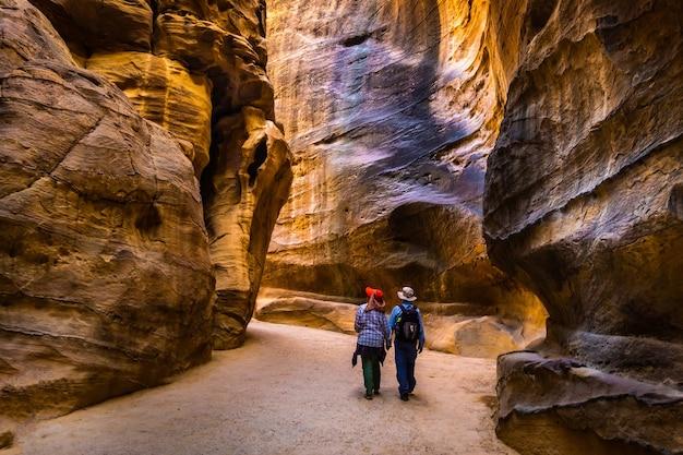 Groupe de personnes entre les rochers de grès au chemin étroit à petra en jordanie