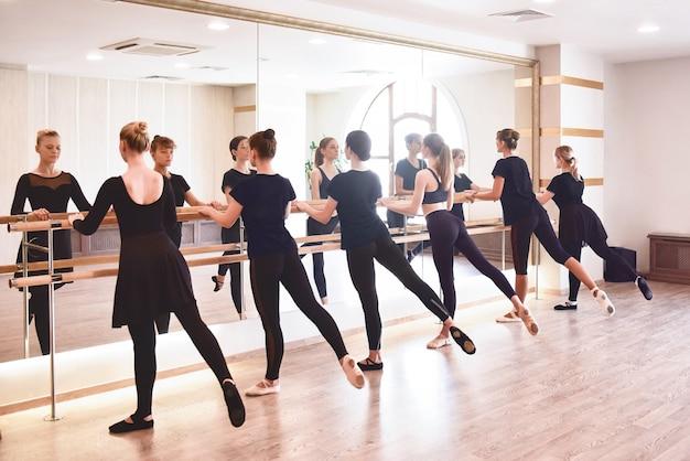Groupe de personnes faisant des exercices à l'aide de la barre dans la salle de sport en mettant l'accent sur l'ajustement de la femme tonique athlétique au premier plan dans le concept de santé et de remise en forme.