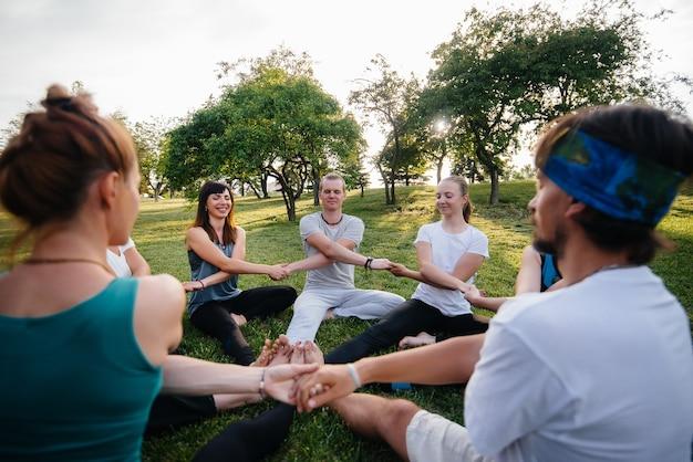 Un groupe de personnes fait du yoga en cercle en plein air au coucher du soleil. mode de vie sain, méditation et bien-être.