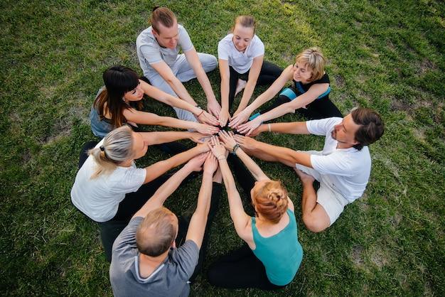 Un groupe de personnes fait du yoga en cercle en plein air au coucher du soleil.
