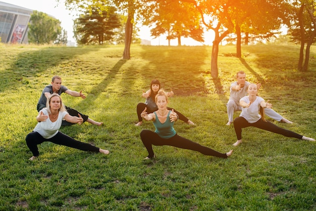 Un groupe de personnes fait du yoga dans le parc au coucher du soleil. mode de vie sain, méditation et bien-être.