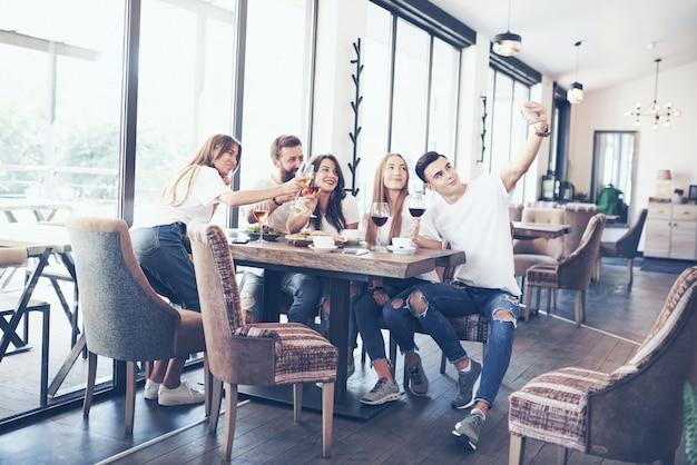Un groupe de personnes fait une photo de selfie dans un café. les meilleurs amis se sont réunis à une table pour manger une pizza et chanter diverses boissons