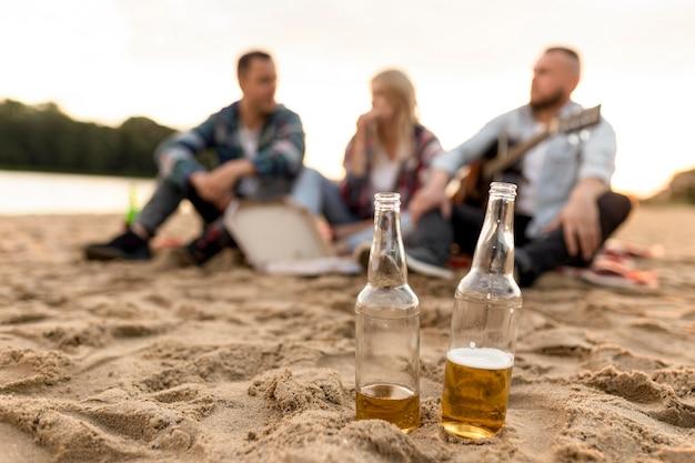 Groupe de personnes floues avec deux bouteilles de bière