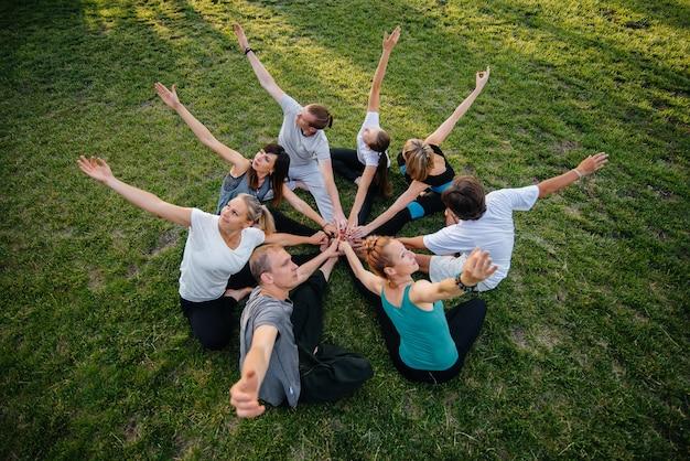 Un groupe de personnes font du yoga en cercle en plein air pendant le coucher du soleil