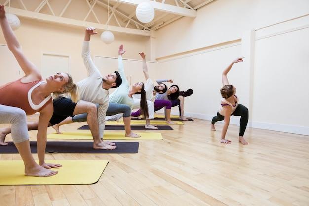 Groupe de personnes formateur aidant avec des étirements exercice
