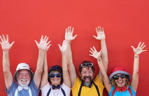 Groupe de personnes heureuses adultes âgées et d'âge moyen avec les bras tendus debout contre le mur rouge