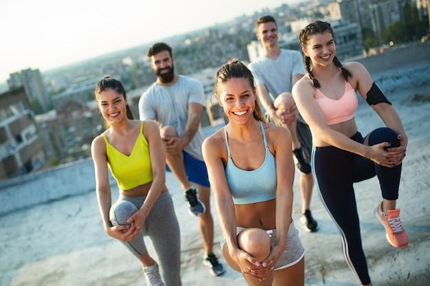 Groupe de personnes heureuses en forme s'entraînant en plein air sur le toit