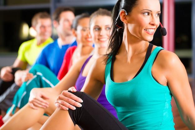 Groupe de personnes et instructeur en gym stretching