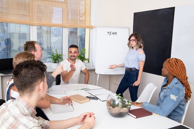 Groupe de personnes internationales regardant la présentation. discussion d'équipe en salle de réunion, table ronde