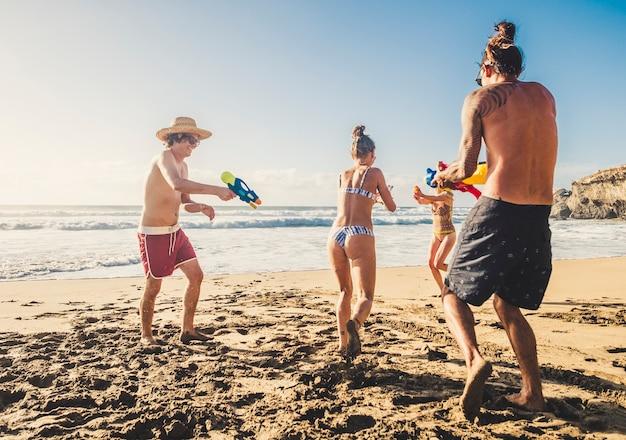 Groupe de personnes jeunes hommes et femmes de race blanche jouent avec un pistolet à eau sur la plage pendant les vacances entre amis ensemble en plein air dans une journée ensoleillée de vacances