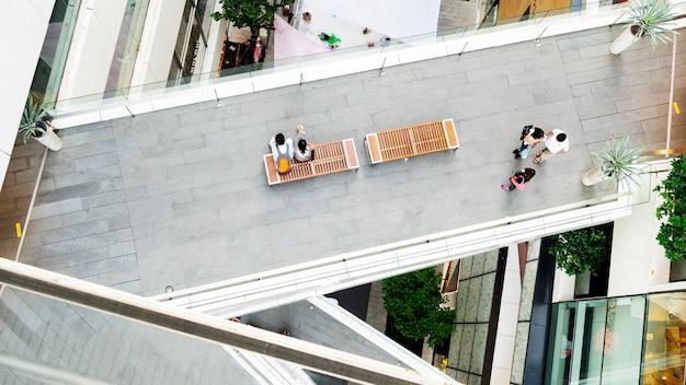 Groupe de personnes marchant et couple d'adolescents assis sur un banc au passage pour piétons