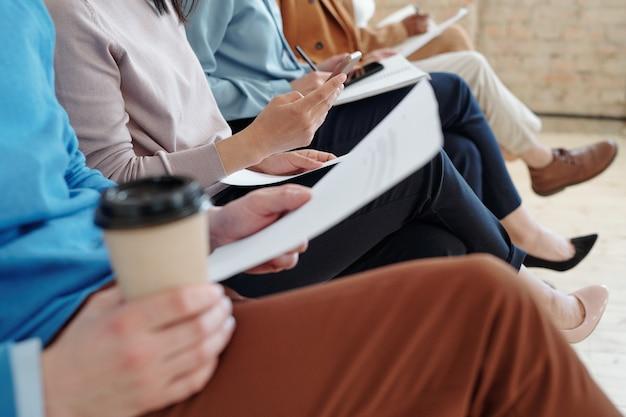Groupe de personnes méconnaissables croisant les jambes et tenant des curriculum vitae en attendant un entretien d'embauche