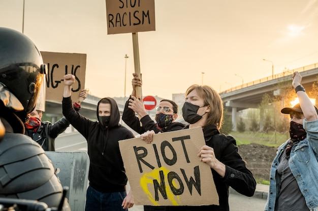 Groupe de personnes mécontentes portant des masques avec des pancartes revendiquant l'égalité des droits pour toutes les ethnies tout en criant contre la police anti-émeute sur la route