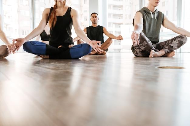 Groupe de personnes méditant en posture de lotus avec les yeux fermés