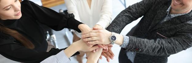 Groupe de personnes mettant leurs mains ensemble en gros plan de bureau