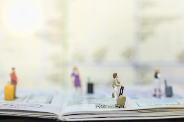 Groupe de personnes miniatures voyageur avec bagages sur passeport