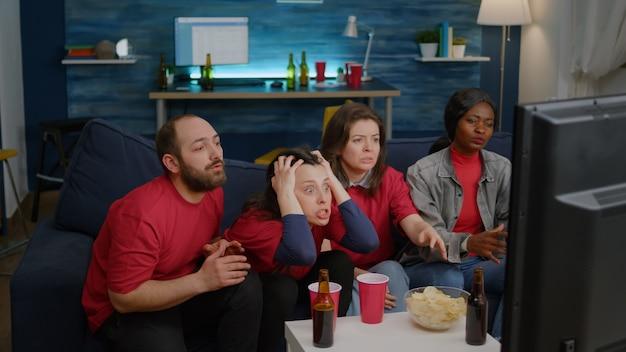 Un groupe de personnes multiethniques frustrés après la défaite d'une équipe de football lors d'une compétition sportive...