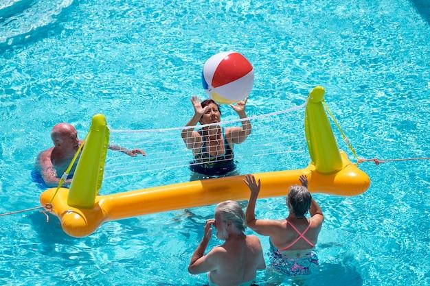 Groupe de personnes mûres profitant de l'été et de la piscine, jouant avec un ballon gonflable et un filet