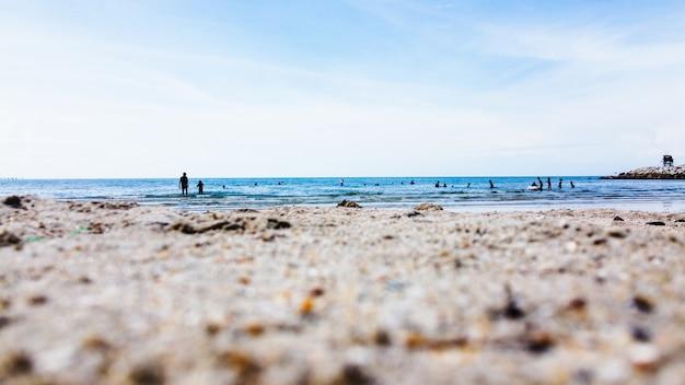 Groupe de personnes nageant sur la plage avec un ciel bleu et gros plan d'une plage de sable.