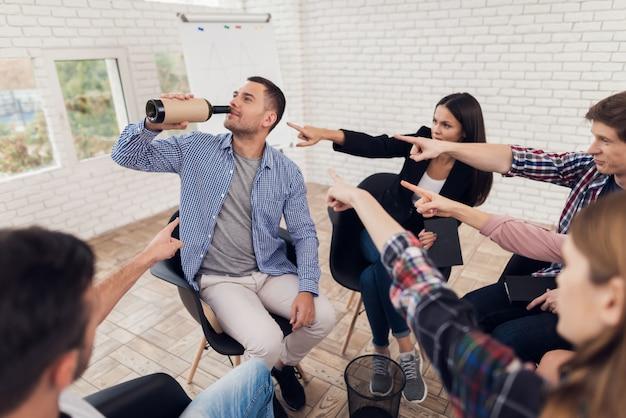 Groupe de personnes pointent du doigt l'homme adulte.