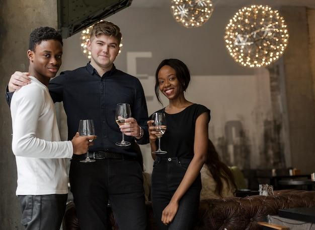 Groupe de personnes positives posant avec du vin