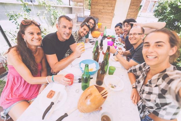 Groupe de personnes prenant selfie tout en déjeunant en plein air