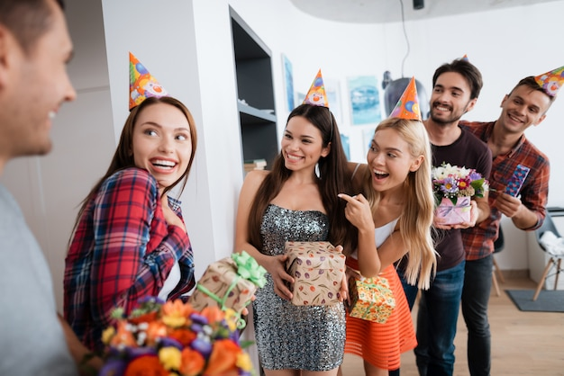 Groupe de personnes prépare une surprise pour fille d'anniversaire.