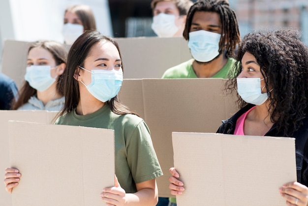 Groupe de personnes protestant et portant des masques médicaux