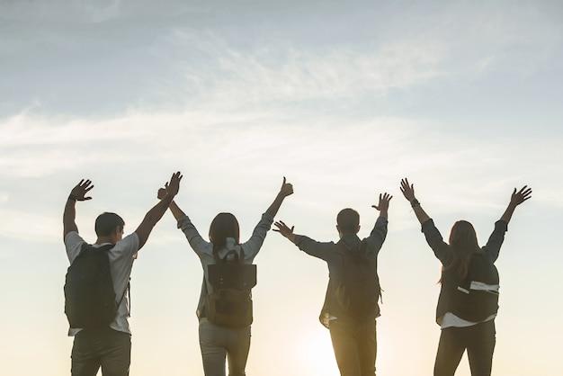 Groupe de personnes de quatre avec des sacs à dos avec les mains levées