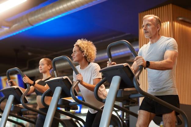 Groupe de personnes qui courent ensemble sur des tapis roulants pendant l'entraînement sportif en salle de sport