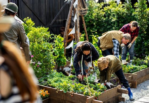 Groupe de personnes qui plantent des légumes en serre