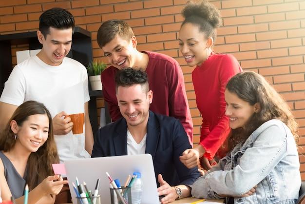 Groupe de personnes de race mixte occasionnels regardant un ordinateur portable discutant du travail