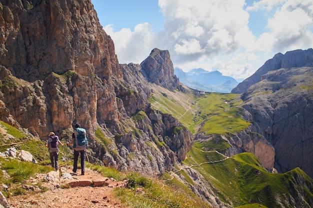 Groupe de personnes en randonnée dans les montagnes du parc naturel schlern-rosengarten en italie